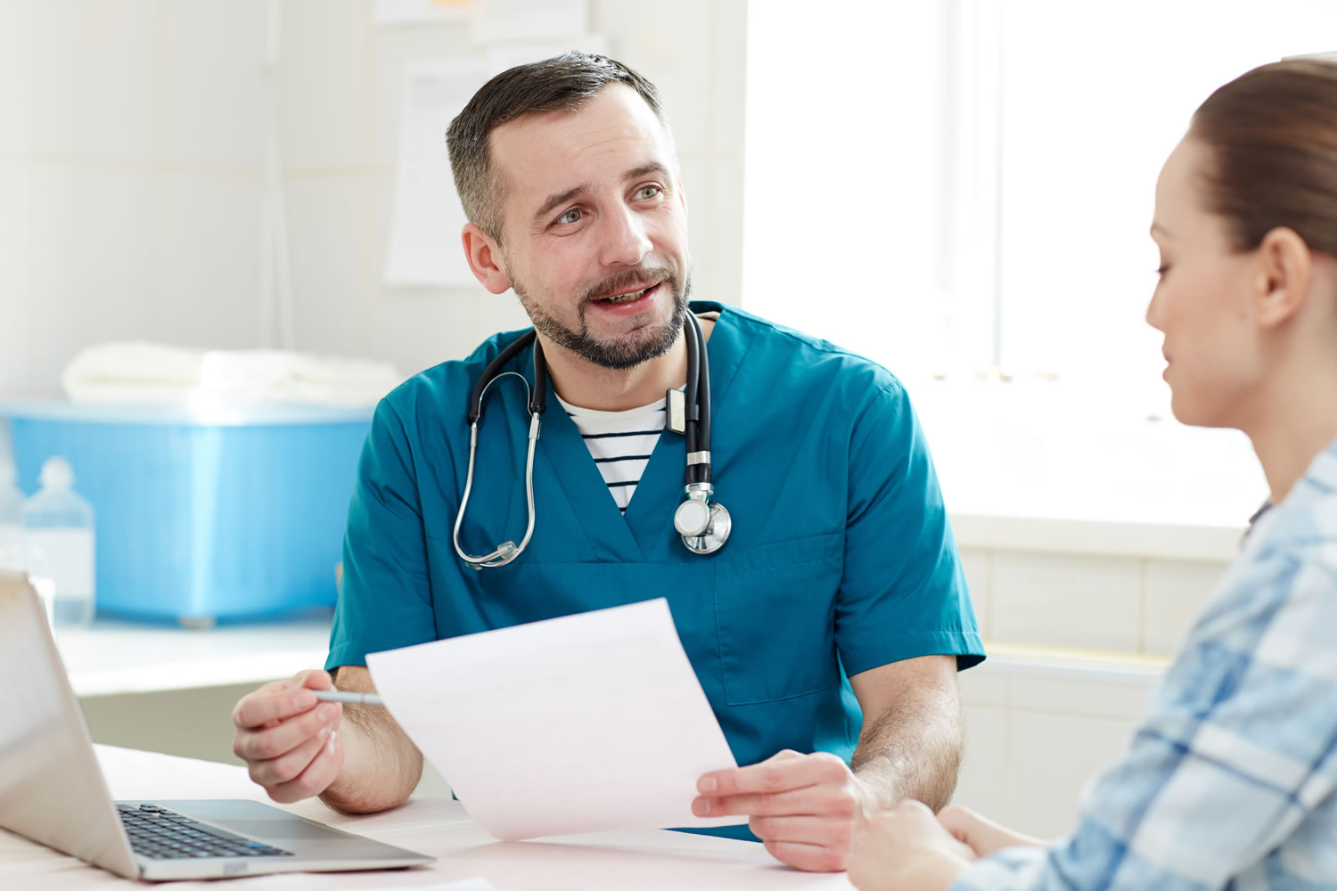 Outpatient doctor and patient sitting down at table discussing paperwork